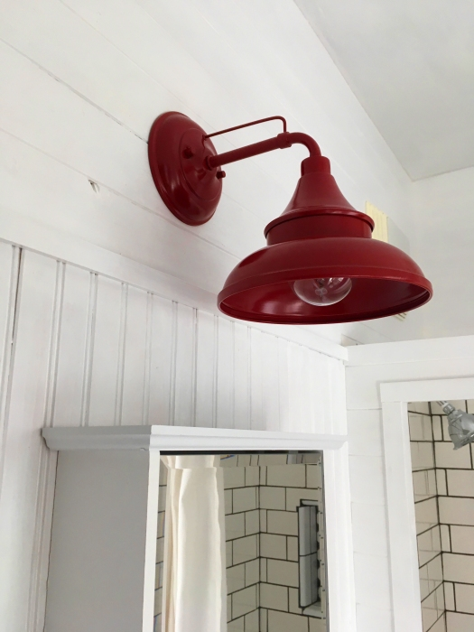 red barn light above medicine cabinet