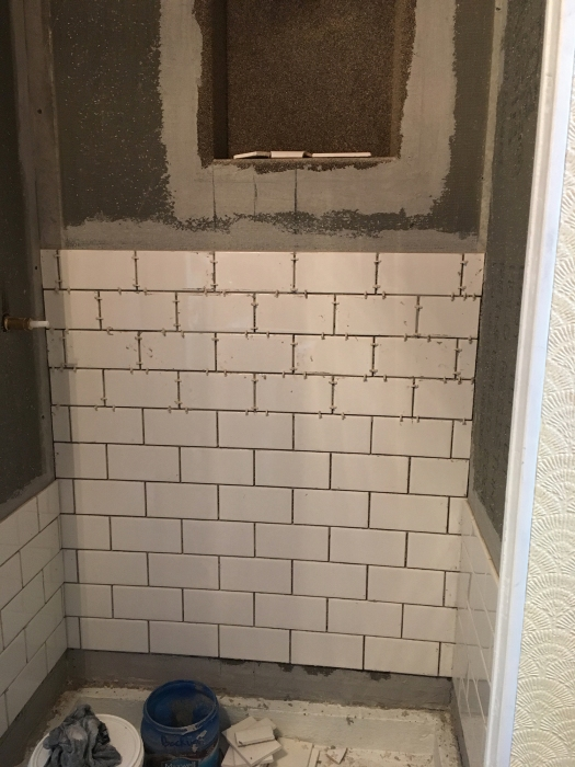 shower stall with subway tile being hung