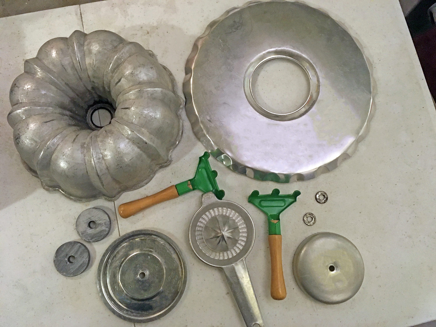 Bundt pan, aluminum juicer, garden trowels and other parts to make a junk turkey assemblage with