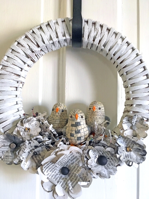 White chalk-painted wicker wreath with newspaper chicks and flowers